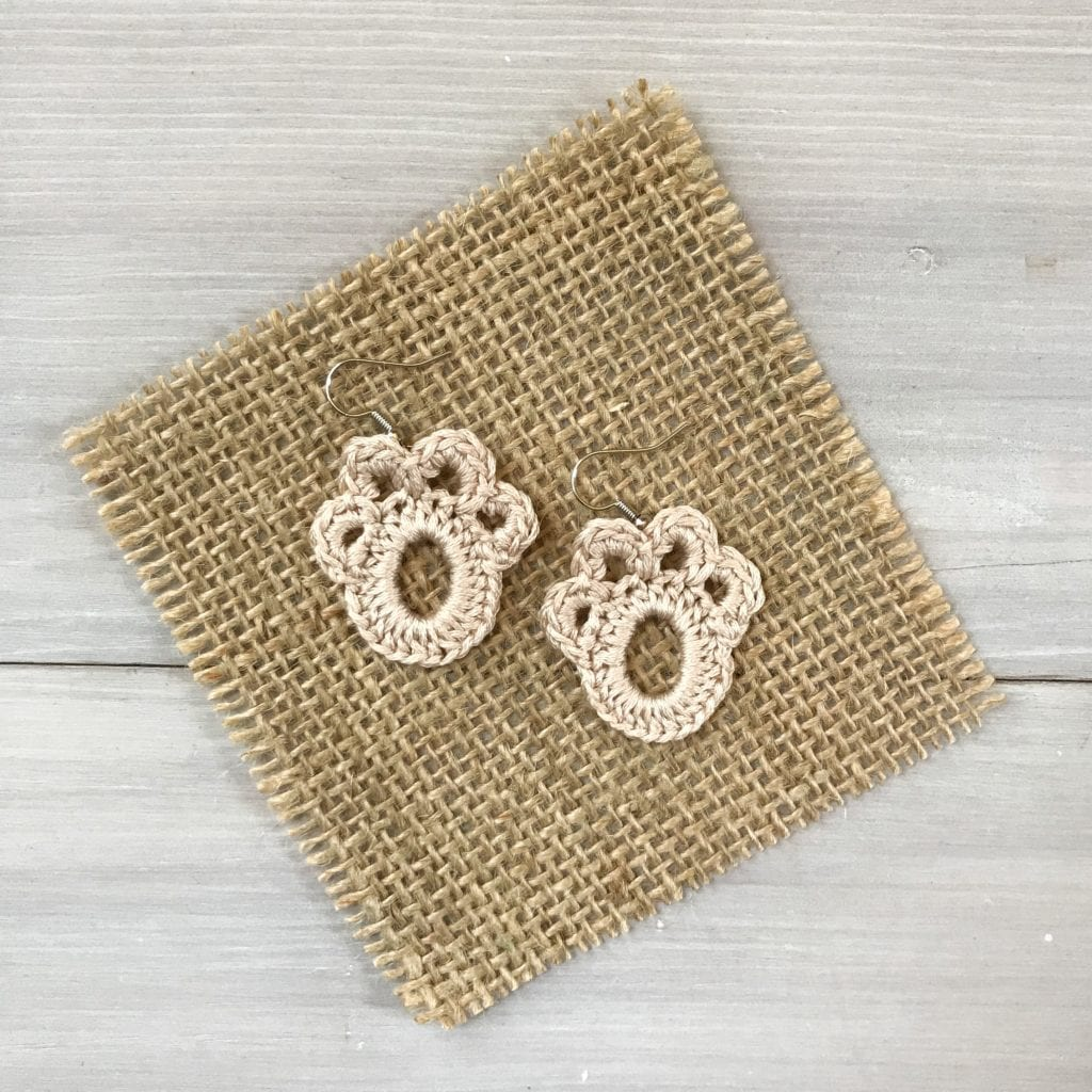 tan crochet paw print earrings displayed flat