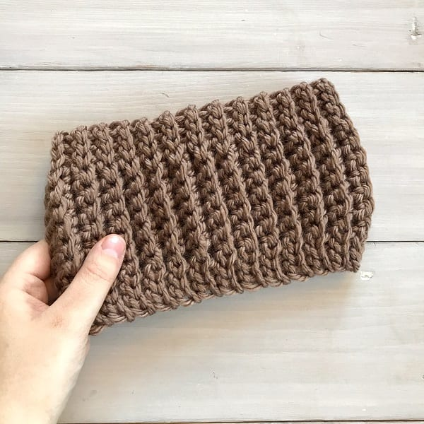 Hand holding a brown crocheted ribbed earwarmer